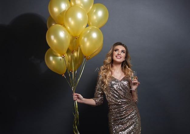 Vrouw met ballonnen en champagne opzoeken Gratis Foto