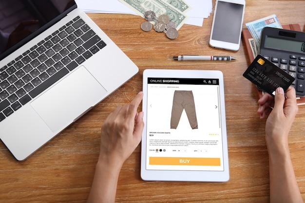 Vrouw met behulp van creditcard voor kopen bruine jogger broek op e-commerce website via tablet met laptop, smartphone en kantoorbenodigdheden op houten bureau Premium Foto