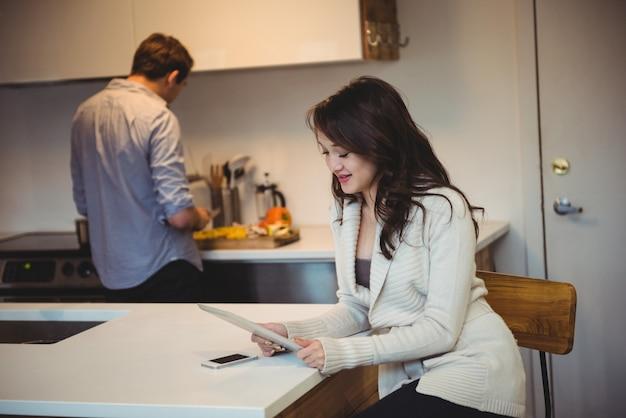 Vrouw met behulp van digitale tablet terwijl man aan het werk op de achtergrond Gratis Foto