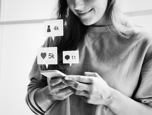 Vrouw met behulp van een smartphone en glimlachen Gratis Foto