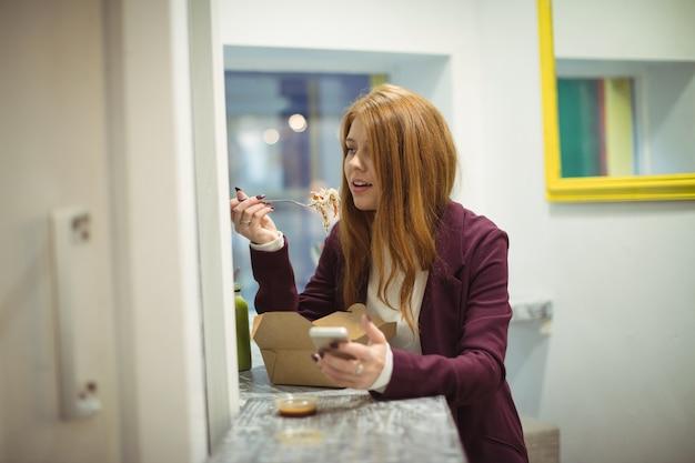 Vrouw met behulp van mobiele telefoon tijdens het eten van salade Gratis Foto