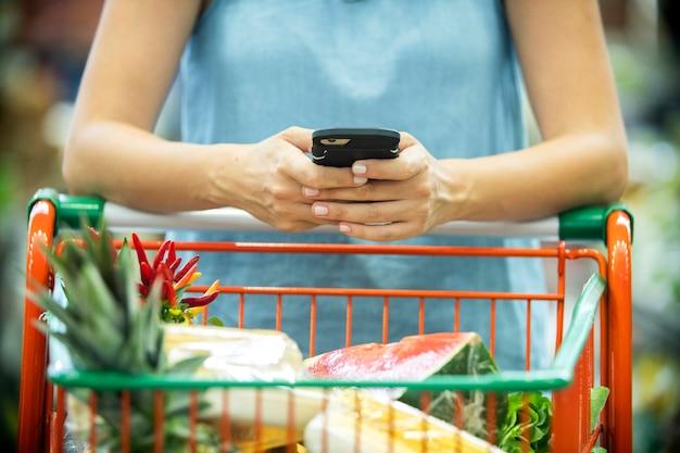 Vrouw met behulp van mobiele telefoon tijdens het winkelen in de supermarkt. Premium Foto