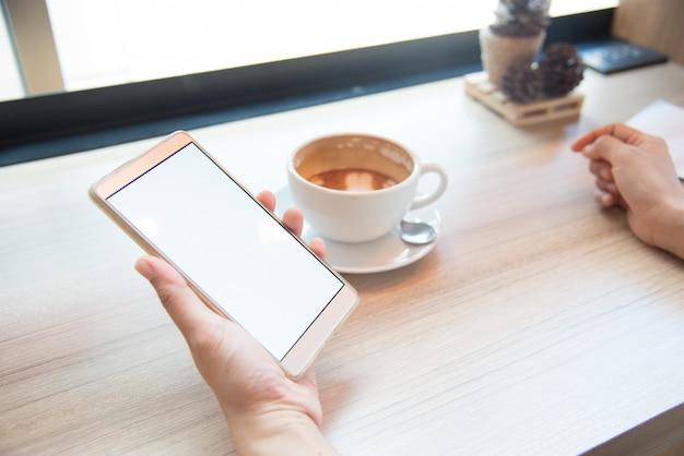 Vrouw met behulp van smartphone, close-up, koffie en planning boek op de achtergrond Premium Foto