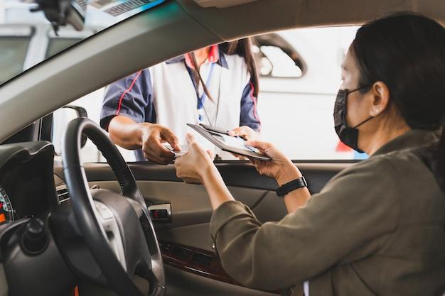 Vrouw met beschermend masker in een auto die benzine met creditcard betaalt bij benzinestation. Premium Foto