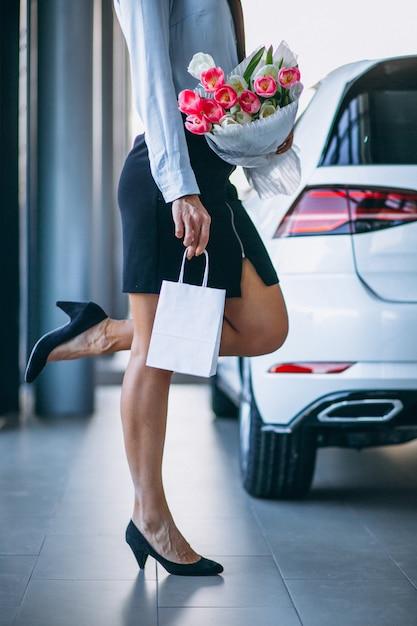 Vrouw met bloemen in een autotoonzaal Gratis Foto