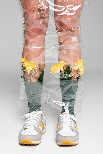 Vrouw met bloemen op sokken bedekt met plastic close-up Gratis Foto
