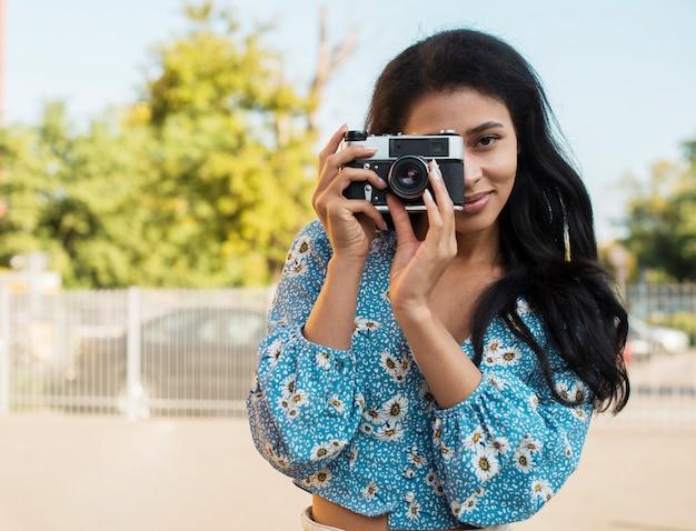 Vrouw met bloemenoverhemd die een foto met een retro camera nemen Gratis Foto