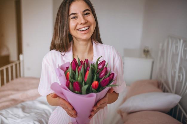 Vrouw met boeket bloemen in de slaapkamer Gratis Foto