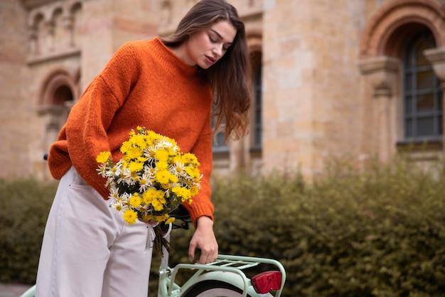 Vrouw met boeket bloemen zittend naast de fiets Gratis Foto