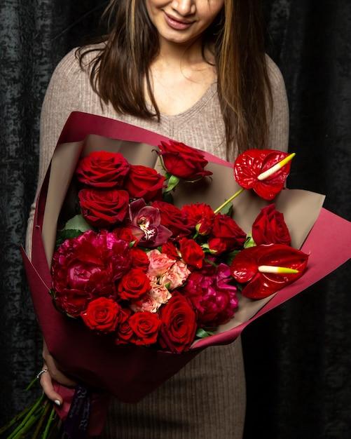 Vrouw met boeket van roze en rode rozen anthurium en pioenrozen Gratis Foto