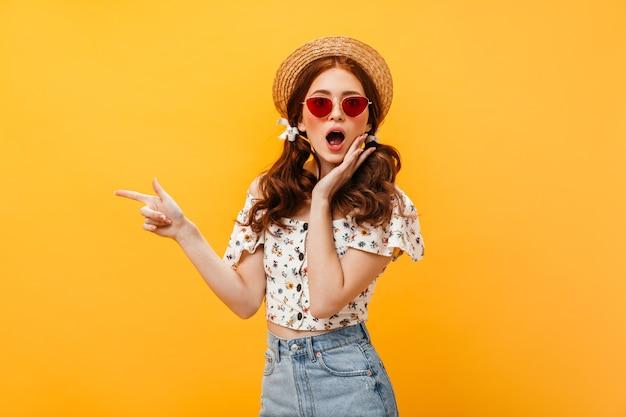 Vrouw met bogen op haar haar en hoed draagt camera kijkt verbaasd. vrouw in rode zonnebril en denim rok wijst vinger naar geïsoleerde achtergrond. Gratis Foto