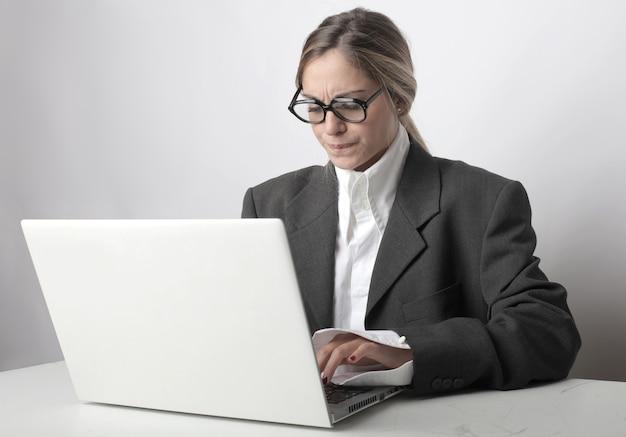 Vrouw met bril en een bezorgd gezicht die op haar laptop op kantoor werkt Gratis Foto