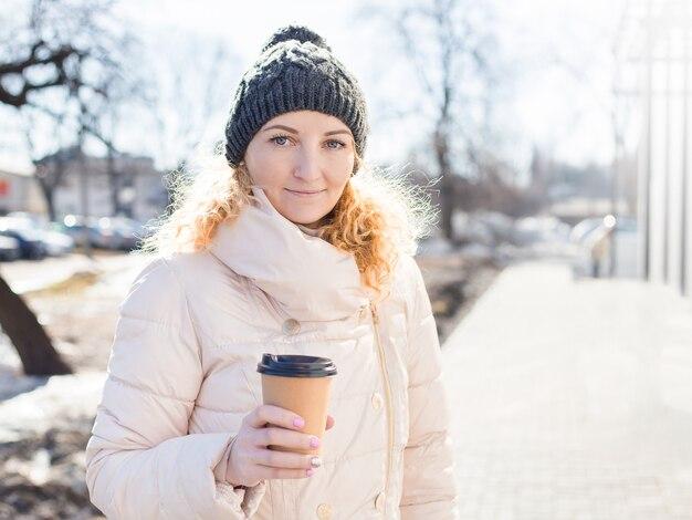 Vrouw met bruine papieren koffiekopje buiten. Premium Foto