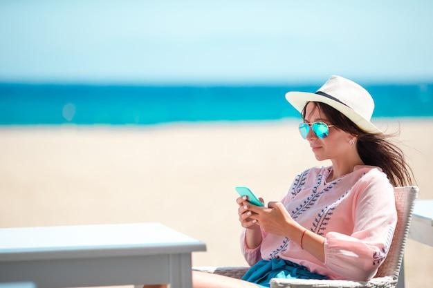 Vrouw met cellphone in openlucht op het strand. toerist met behulp van mobiele smartphone. Premium Foto