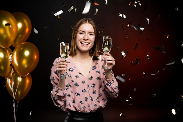 Vrouw met champagneglazen omgeven door confetti en ballonnen Gratis Foto