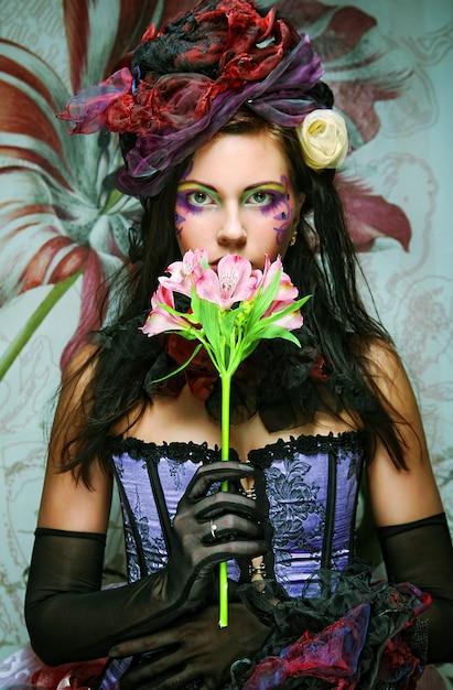 Vrouw met creatieve make-up in poppenstijl met bloem Premium Foto