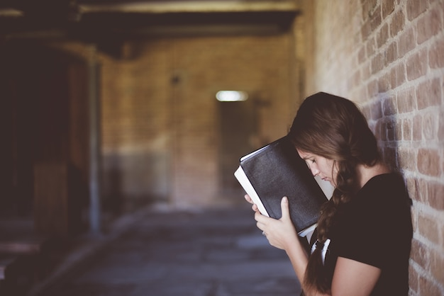 Vrouw met de bijbel tegen haar hoofd tijdens het bidden Gratis Foto