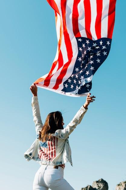 Vrouw met de golvende vlag van de vs op blauwe hemel Gratis Foto