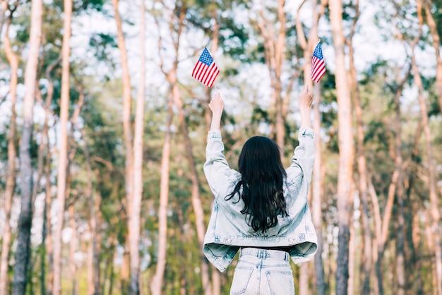 Vrouw met de vlaggen van de vs in uitgestrekte handen Gratis Foto