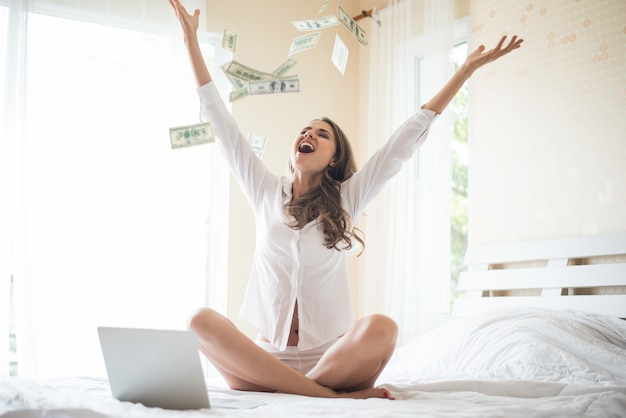 Vrouw met dollarbankbiljet op het bed Gratis Foto