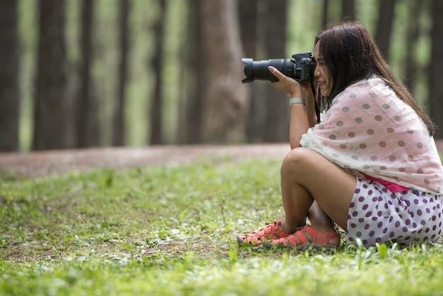 Vrouw met dslr camera-opnamen poseren Premium Foto