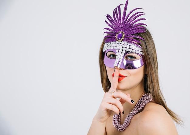 Vrouw met een carnaval-masker die stiltegebaar op witte achtergrond maken Gratis Foto
