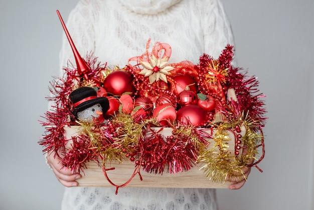 Vrouw met een doos met rode kerstversieringen Gratis Foto