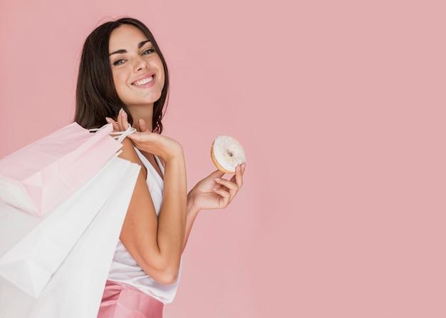 Vrouw met een doughnut met witte chocolade en winkelnetten Gratis Foto