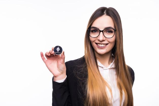 Vrouw met een fysieke cryptocurrency van ethereum-munten in haar hand Gratis Foto
