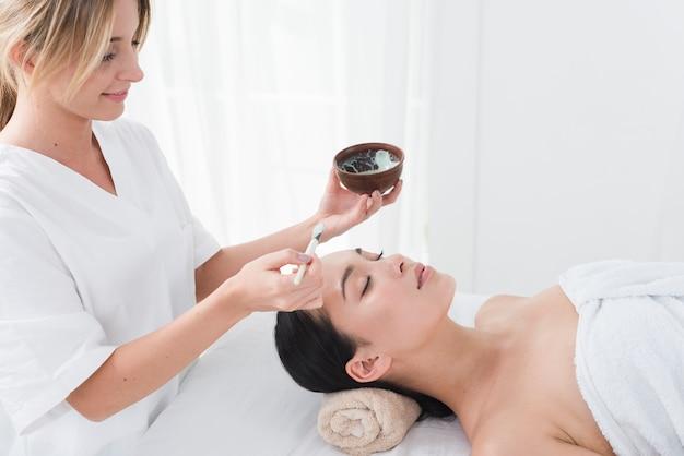 Vrouw met een gezichtsmasker in een spa Gratis Foto