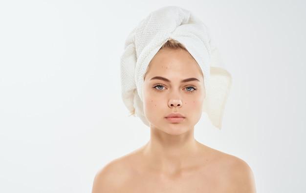 Vrouw met een handdoek op haar hoofd naakte schouders nat haar problemen we worden geconfronteerd met huid. Premium Foto