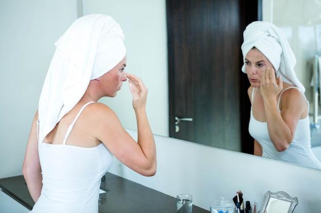 Vrouw met een handdoek op haar hoofd past gezichtscrème toe Premium Foto