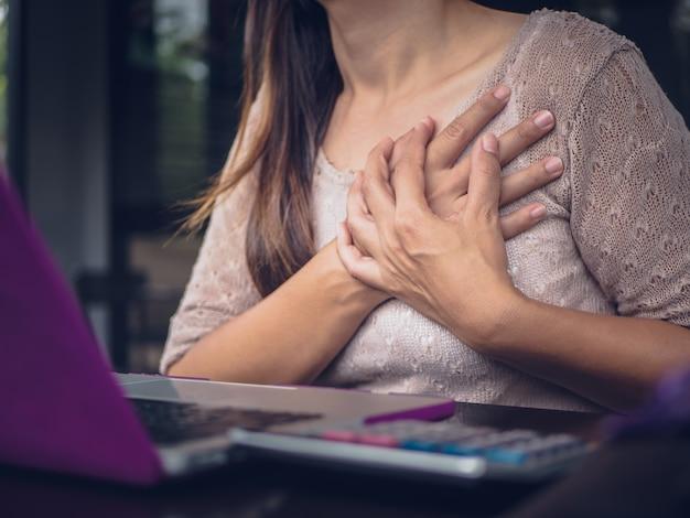 Vrouw met een hartaanval. vrouw wat betreft borst en hebbend borstpijn Premium Foto