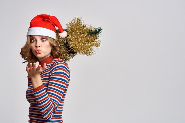 Vrouw met een kerstboom in haar hand gele klatergoud vakantie glb geschenken Premium Foto