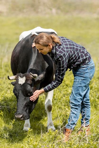 Vrouw met een koe op de boerderij Gratis Foto