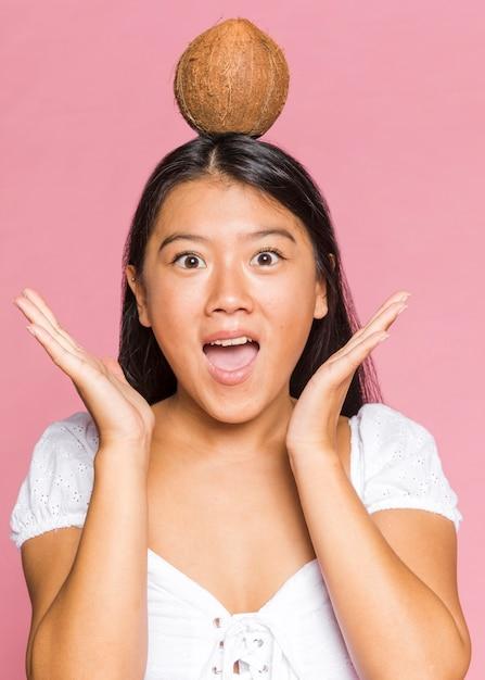 Vrouw met een kokosnoot op haar hoofd Gratis Foto