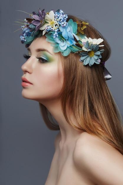 Vrouw met een kroon van blauwe bloemen op haar hoofd Premium Foto