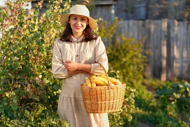 Vrouw met een mand met een oogst van maïs in haar hand. Premium Foto