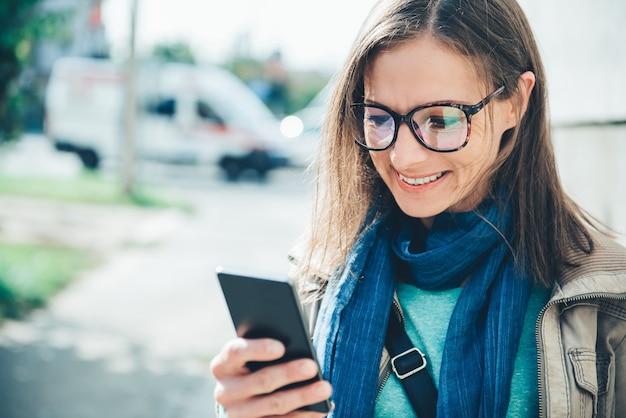 Vrouw met een mobiele telefoon op straat Premium Foto