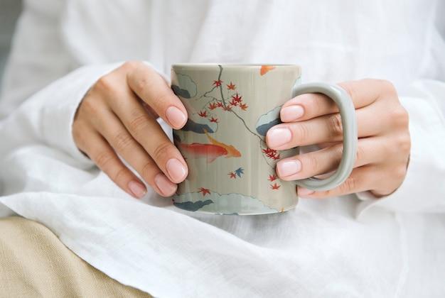 Vrouw met een mok van de japanse patroonkoffie, remix van kunstwerk door watanabe seitei Gratis Foto
