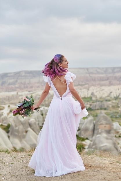 Vrouw met een mooi boeket bloemen in haar handen dansen op de berg in de stralen Premium Foto