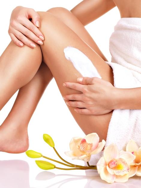 Vrouw met een mooi lichaam met een crème op haar been op een wit Gratis Foto