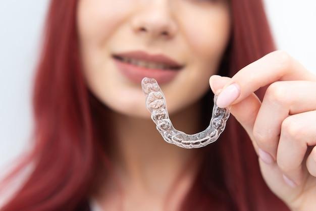 Vrouw met een mooie glimlach toont een transparante gebitsbeschermer Premium Foto