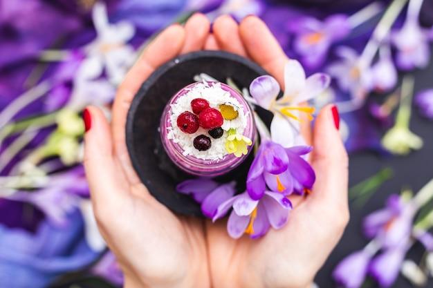 Vrouw met een potje veganistische smoothie gegarneerd met bessen, omgeven door paarse lentebloemen Gratis Foto