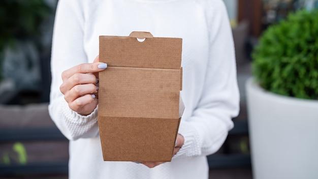 Vrouw met een recyclebare papieren voedseldoos. recycling idee Gratis Foto