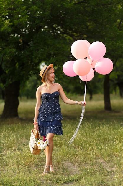 Vrouw met een rieten mand, hoed, roze impulsen en bloemen die op een landweg lopen. Premium Foto