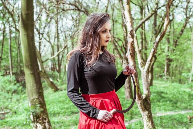 Vrouw met een sikkel in bos Premium Foto