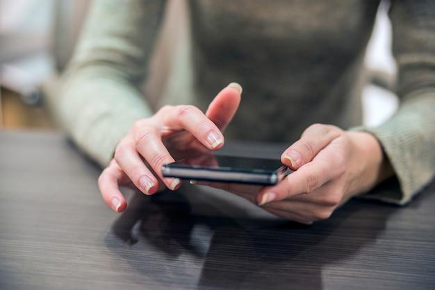 Vrouw met een smartphone op de houten tafel. close-up handen van het meisje, zitten aan de houten tafel, in de ene hand is smartphone. zakenvrouw surfen op internet op smartphone. Gratis Foto