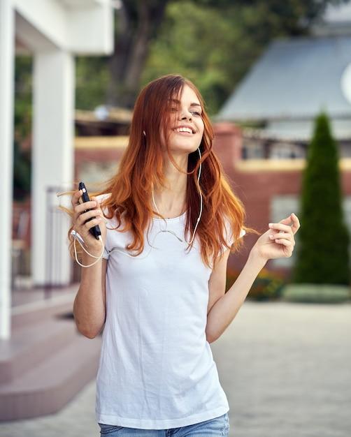 Vrouw met een telefoon in hoofdtelefoon loopt Premium Foto