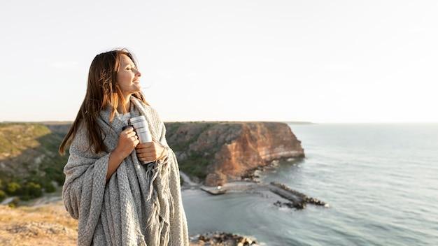 Vrouw met een thermoskan tijdens het wandelen op een kust met kopie ruimte Gratis Foto